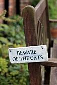 A sign on a garden bench