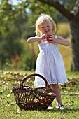 Blondes Mädchen mit Apfel im Garten