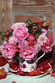 An autumnal bouquet of flowers wih roses and asters