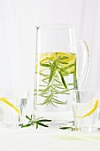 A jug of water with lemon slices and a rosemary sprig