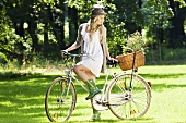 A blonde woman on a bike in a park
