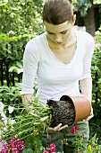 Young woman re-potting plants