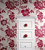 A white chest of drawers with tomatoes as knobs