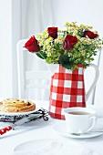 Kanne als Blumenvase, Tee und Kuchen