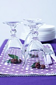 Washed glasses with blackberries underneath them on napkins