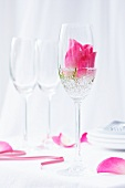A rose in a champagne glass with decorative stones