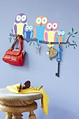 Owl wall stickers, key hooks, a bag and a scarf and sunglasses on a stool