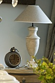 Alarm clock and lamp on a bedside table