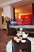 Tea things, flower arrangement & soap on small table in living room