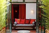 Sofa with cushions in front of opened terrace door