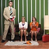 Zwei Frauen und ein Mann mit Kaffee im Wohnzimmer