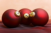 Three dark red Christmas baubles