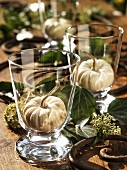 Ornamental gourds in glasses (autumn table decoration)