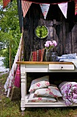 Books and garden cushions on table out of doors