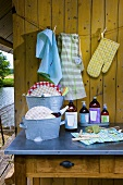 Bottles, tubs and crockery on a table outside a wooden cabin
