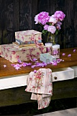 Boxes, books, peonies and candles on a table