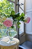 Roses in glass vase on occasional table by window