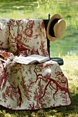 Romantic garden seat with cover, book and straw hat by pond