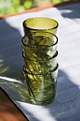 Green drinking glasses, stacked, on table out of doors
