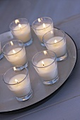 Several candles in glasses on plate