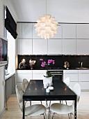Küche in Weiss und Schwarz mit Esstisch, Küchenstühlen & moderner Deckenleuchte