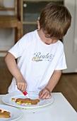 Boy decorating a gingerbread man