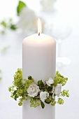 White candle with wreath of lady's mantle and white roses