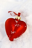 Heart-shaped Christmas tree ornament in snow