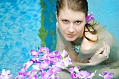 Young woman in swimming pool with flowers