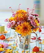 Chrysanthemums and bell heather in mug