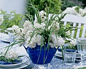 Blue and white table decoration with lilac and grasses