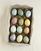 Marbled Easter eggs in wooden box with straw