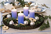 Juniper sprigs with tree ornaments & four candles in baking tin