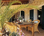 Laid wooden table with rattan armchairs on a veranda