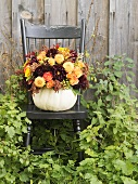 Autumn flowers in hollowed-out pumpkin on a garden chair