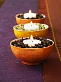 Three bowls of spices with candles