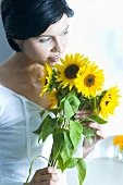 Young woman with a bunch of sunflowers