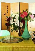 Esstisch mit Blumendeko, im Hintergrund Chinesischer Paravent