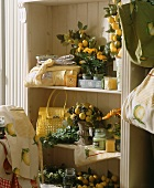 A shelf with garden and patio decorations (lemons, candles etc)