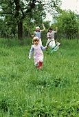Three girls skipping through the grass