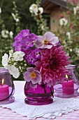 A pink bouquet and lanterns on a garden table