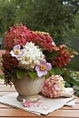 An autumnal bouquet of hortensias on a garden table