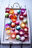 Christmas tree baubles and tea lights in a tray