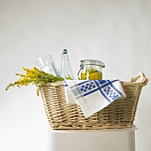Pickled vegetables, flowers and a bottle of water in a basket