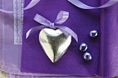 Silver heart with a bow on a purple surface