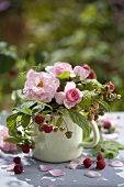 Summery table decoration of roses and raspberries