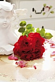 A small round bouquet of red roses beside an angel bust