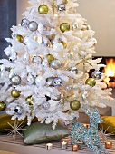 White artificial Christmas tree in front of open fire