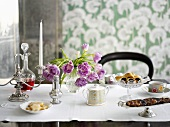 Table laid for coffee with candlestick and vase of flowers