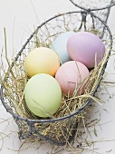 Easter eggs on hay in wire basket
